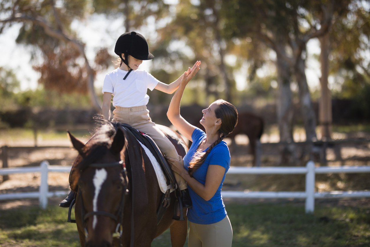 Side view of woman giving high five to girl sitting on horse